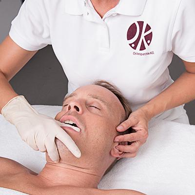 Frau Hörster behandelt einen Patienten im Kopf- und Kieferbereich mit einer manuellen Technik, bei der Sie mit einer Hand an das Ohr und mit der anderen Hand an den Unterkiefer greift.