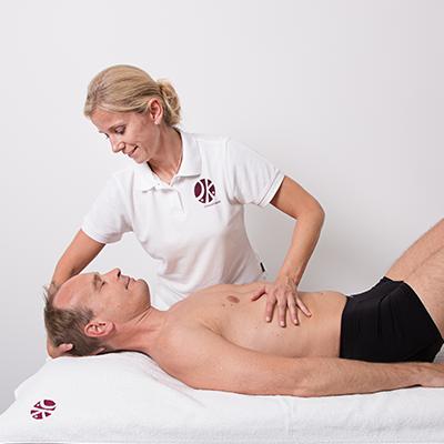 Frau Hörster in einer osteopathischen Behandlung bei der Sie die eine Hand unter den Kopf und die andere Hand auf den Bauch des Patienten legt.