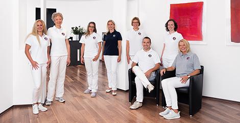 Vorstellung des Praxisteams Osteopathie.Kö., teilweise sitzten die Therapeuten auf den Stühlen im Wartezimmer, teilweise stehen sie vor dem Empfangstresen im Eingangsbereich.