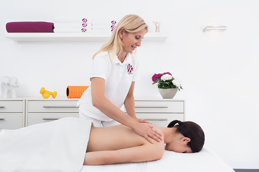 Frau Hörster behandelt eine Patientin, die auf dem Bauch liegt, mittels Osteopathie indem Sie eine spezielle Technik im Schulter-/Nackenbereich durchführt.