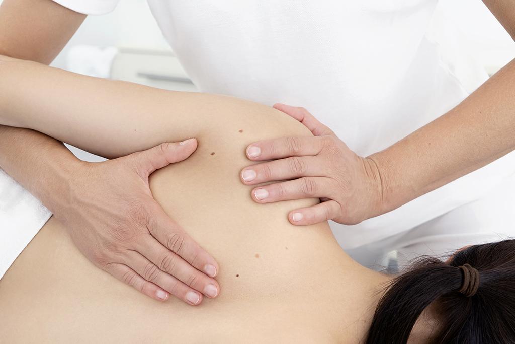 Frau Hörster behandelt die Schulter einer Patientin mittels einer osteopathischen Technik.