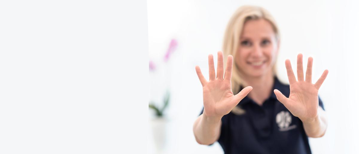 Frau Anett Hörster streckt Ihre heilenden Hände nach vorne, so dass man diese im Vordergrund und sie selbst leicht unschaft im Hintergrund sieht.