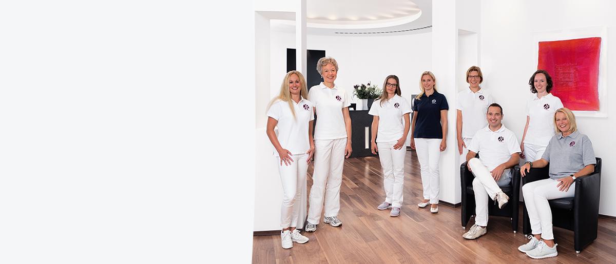 Das gesamte Praxisteam mit 8 Personen ist abgebildet, teilweise auf den Wartestühlen sitzend, teilweise vor dem Empfangstresen stehend.