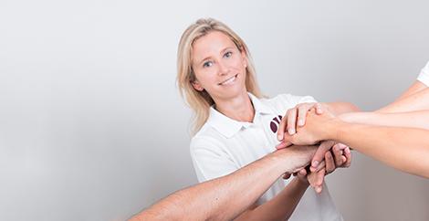 Anett Hörster hält ihre Hände nach vorne ausgestreckt, wo sie mit den Händen vom restlichen Therapeutenteam übereinander liegen und so das Team Work in der Praxis symbolisieren.